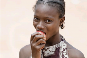 African girl smiling and eating an apple
