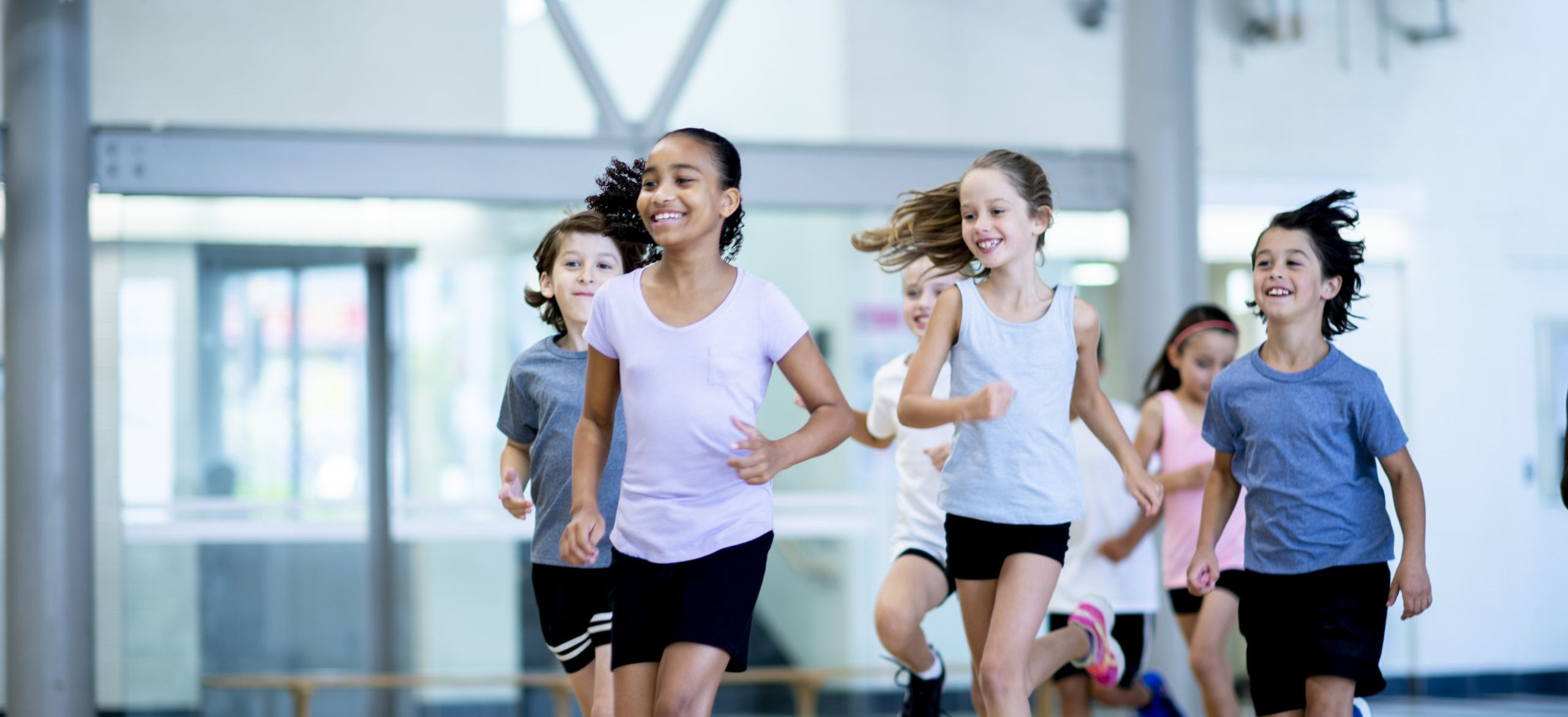 A group of diverse kids run through the gym while laughing.