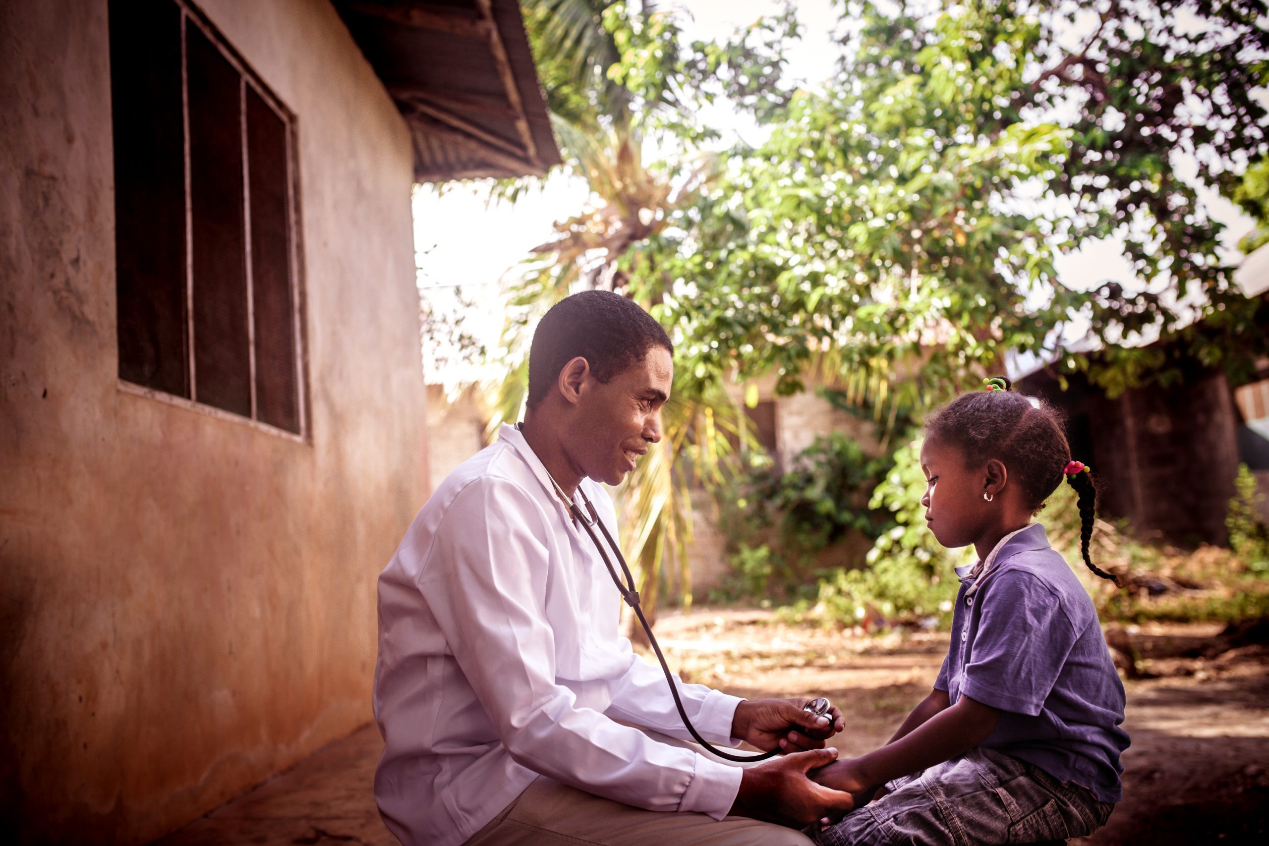 African doctor using stethoscope on a child in a village