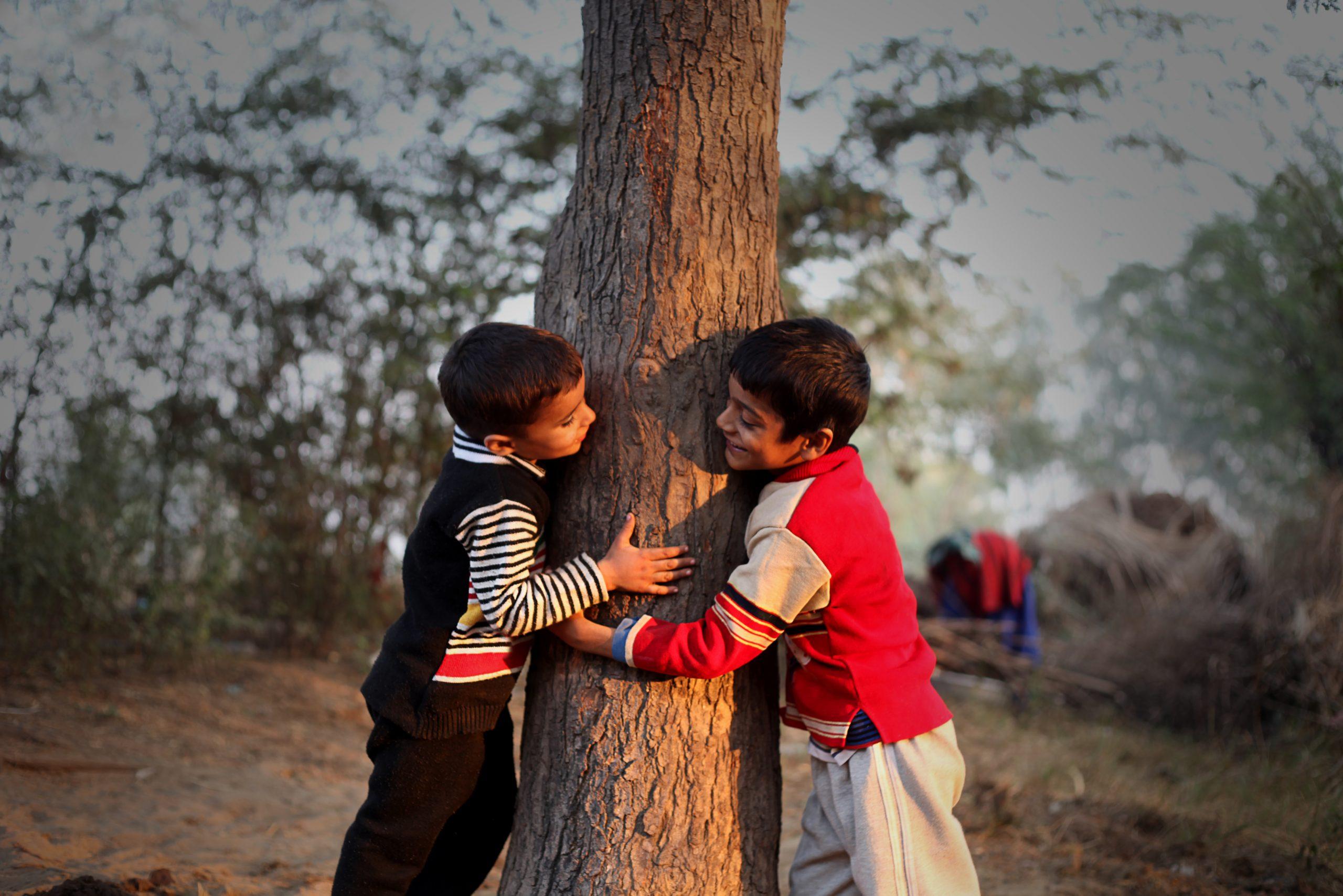 Playful children holding tree trunk