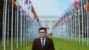 young man smiling in front of a yard with flags of all the nations